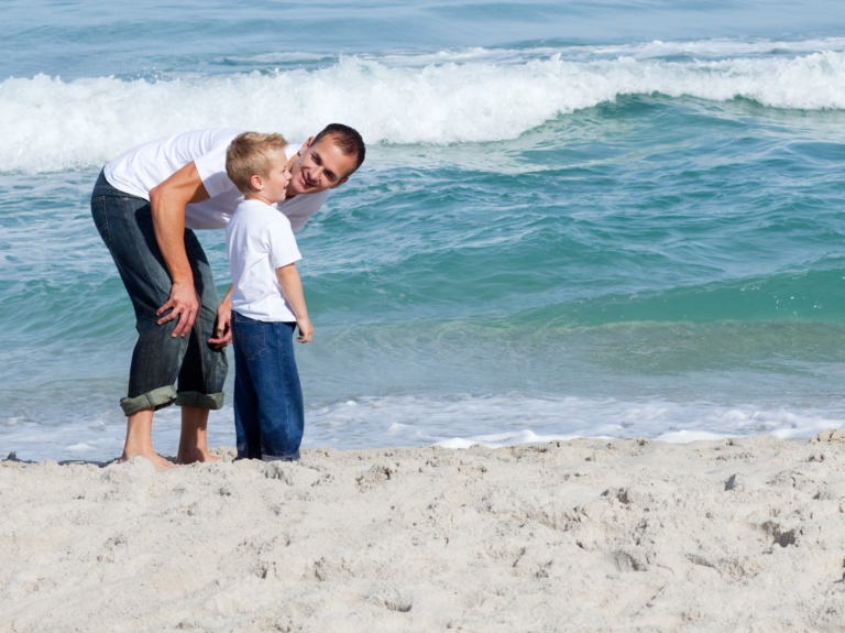 father talking with son at ocean